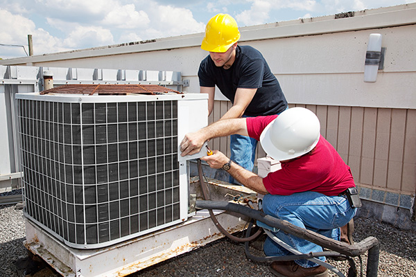 Men repairing industrial air conditioner